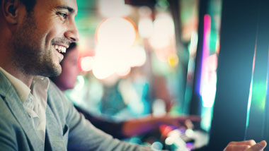 man playing slot, person faded in background