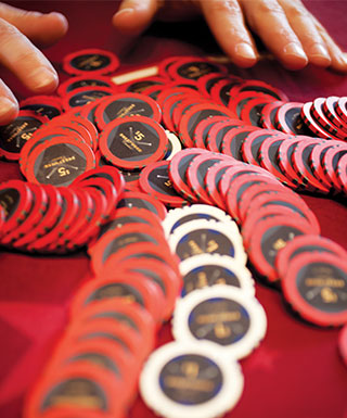 hands with scattered chips on red table